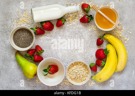 Healthy breakfast ingredients: Oatmeal, honey, fruit, strawberry and chia seeds.Top view with copy space. concept - Stock Photo