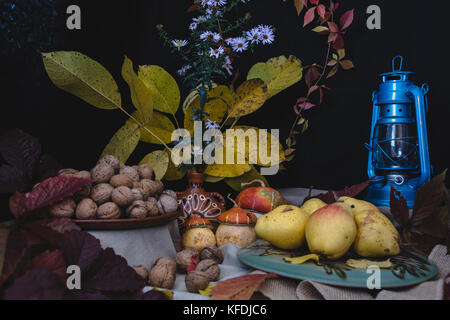 The autumn still life is decorated with a pear, walnut, pumpkin, autumn leaves and a kerosene lamp - Stock Photo