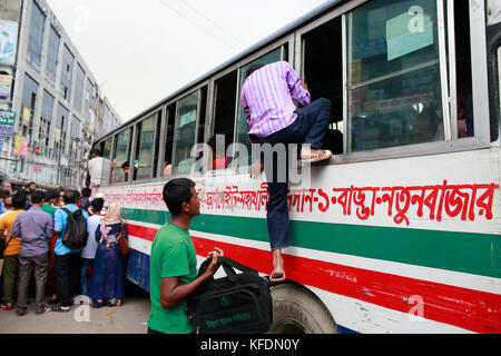 Bangladeshi people try to ride in of an overcrowded bus to travel home, as others wait for transport ahead of Iftar, - Stock Photo