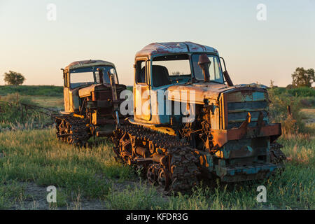 Very old rusted tractor in a green field under a blue sky in the summer time, old rusted tractor on the grass - Stock Photo