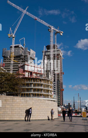 Banking workers having a lunch-time break by new office and residential construction site  in Canary Whart,London,UK - Stock Photo