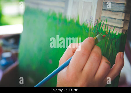Artist holding paint brush painting canvas - Stock Photo