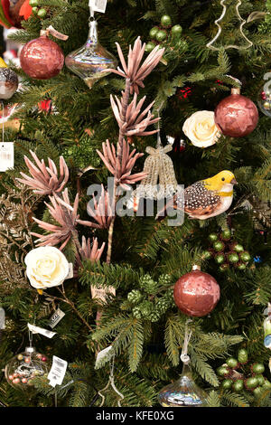 Various baubles and christmas decorations on an xmas tree including a small yellow bird and some brightly coloured - Stock Photo