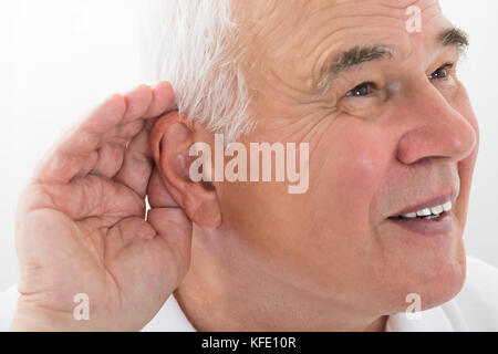 Senior Man Trying To Hear With Hand Over Ear - Stock Photo