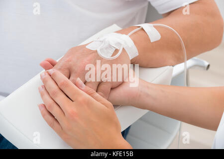 Close-up Of A Doctor Holding Patient's Hand With Iv Drip - Stock Photo