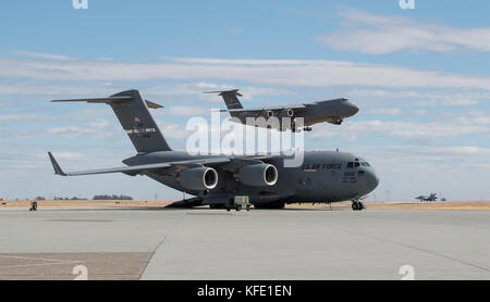 C-5 M Super Galaxy from Dover Air force Base, Delaware, makes its final approach as a -17 Globemaster III parked - Stock Photo