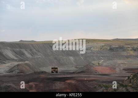 A lone coal mining truck inside of a vast open pit coal mine in the Powder River Basin of Wyoming, USA - Stock Photo