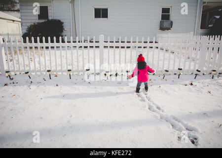 Infant standing in snow wearing winter clothes - Stock Photo