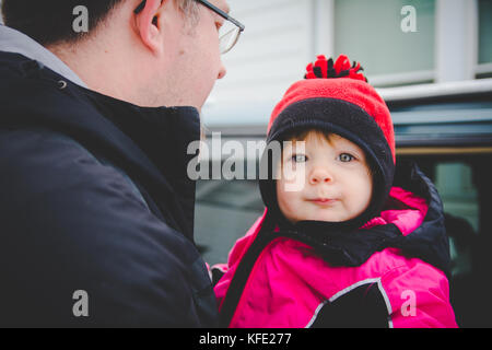 Man carrying child to car in winter clothes - Stock Photo