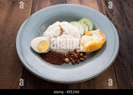 malaysian food/cuisine (nasi lemak) - white rice with fried egg,anchovies,spicy sauce (sambal) and peanuts all put - Stock Photo