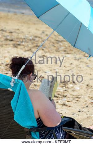 Woman reading on beach, Swanage, Dorset, England, UK - Stock Photo