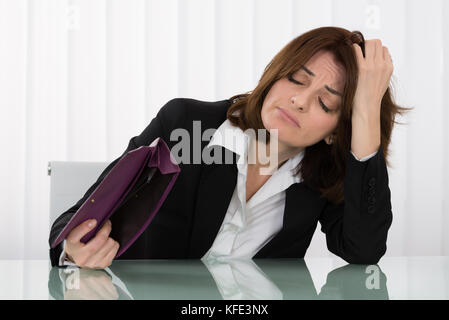 Sad Young Businesswoman Holding Empty Purse At Desk - Stock Photo