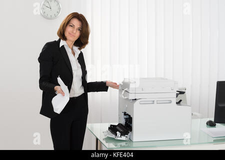 Unhappy Businesswoman Holding Crumpled Paper Standing Near Photocopy Machine - Stock Photo