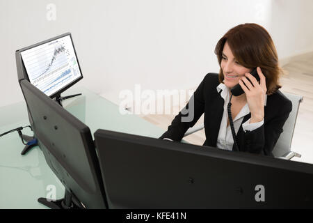 Smiling Young Female Stock Market Broker Working On Multiple Computers While Talking On Phone - Stock Photo