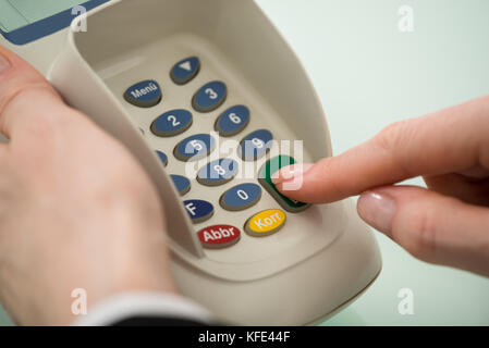 Close-up Of Woman Hand Pressing Button On Credit Card Machine - Stock Photo