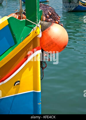 Traditional fishing boats of Malta called Luzzu or Dghajsa in the fishing village of Marsaxlokk - Stock Photo