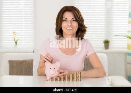 Woman Inserting Coin In Piggybank In Front Of Stacked Coins - Stock Photo