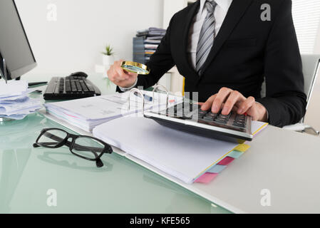 Photo Of Businessman Analyzing Bills With Magnifying Glass - Stock Photo