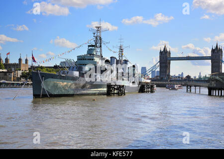 HMS belfast on the banks of the river thames in london with tower bridge behind - Stock Photo