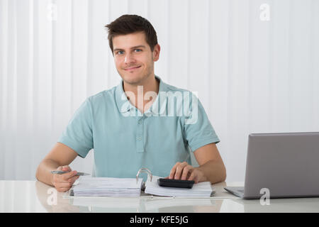 Photo Of Young Man Calculating Tax At Home - Stock Photo