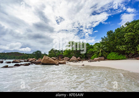 a cloudy sky over the paradise beach with granite rocks, white sand and palm trees  at anse lazio on praslin on - Stock Photo