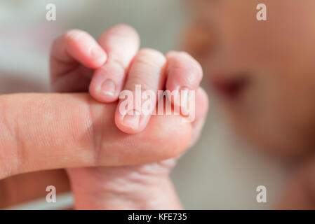 Close-up Photo Of Baby Holding Mother's Finger - Stock Photo