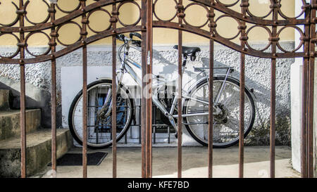 Cetinje, Montenegro - A bicycle leaning up against the house wall behind a backyard gate - Stock Photo