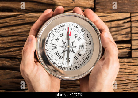 Close-up Of A Hands Holding Magnetic Compass Over The Wooden Desk - Stock Photo