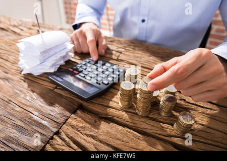 Close-up Of A Business Person Counting Coins Using Calculator With Pink Piggybank Over The Desk - Stock Photo