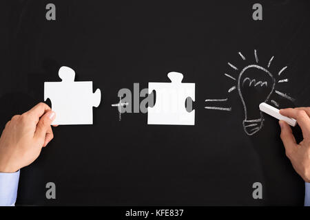Person Drawing Idea Equation With White Puzzles On Black Blackboard - Stock Photo
