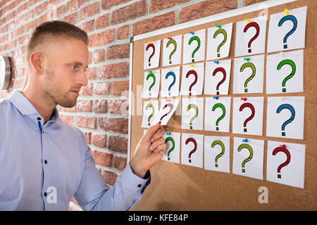 Close-up Of A Businessman Looking At Question Marks On Notes Attached Over Bulletin Board - Stock Photo