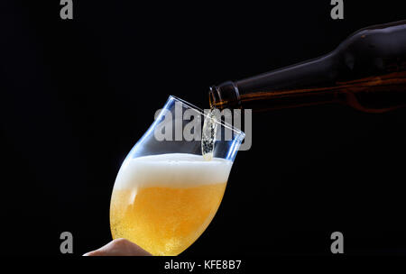 Pouring beer in a glass closeup on a black background. - Stock Photo