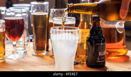 Man's hand pouring beer in an empty frosty glass of beer on a pub background - Stock Photo