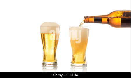 Bottle of beer pouring beer in a glass on white background - Stock Photo