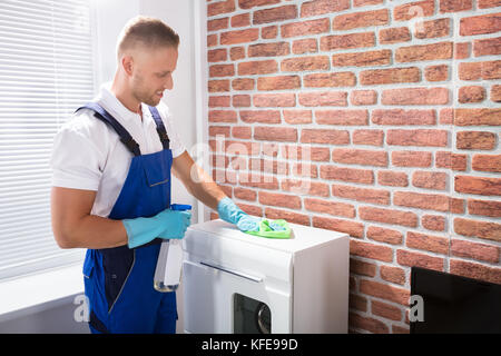 Happy Male Janitor In Uniform Cleaning The Furniture With Rag And Spray - Stock Photo