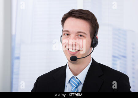 Portrait of confident young businessman wearing headset in office - Stock Photo
