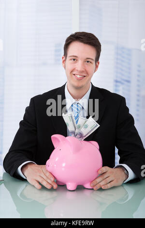 Portrait of young businessman holding piggybank at office desk - Stock Photo