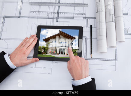 Cropped image of male architect using digital tablet on blueprint in office - Stock Photo