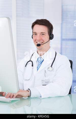 Portrait of young male doctor wearing headset while using computer at desk in clinic - Stock Photo