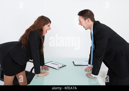 Side view of angry business people shouting at each other in office - Stock Photo