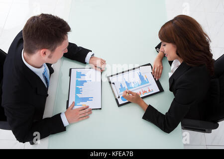 High angle view of young business people discussing over graphs in office - Stock Photo