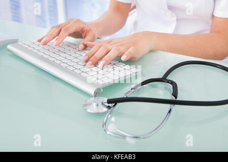 Midsection of female doctor typing on computer keyboard in clinic - Stock Photo