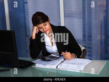 Stressed young businesswoman working at computer desk in office - Stock Photo