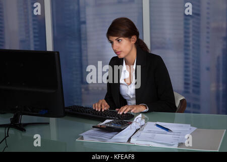 Tired young businesswoman working late in office - Stock Photo