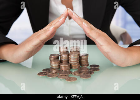 Midsection of businesswoman sheltering coins in house shape on desk - Stock Photo