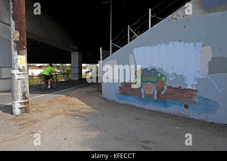 Cyclist riding by frog wall mural painting on the Glendale Freeway Bridge in Frogtown in Elysian Valley NE Los Angeles - Stock Photo