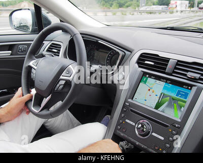 Driver driving  with navigation on road at sunny day - Stock Photo