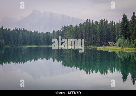 Cabin in front of Mount Rundle at Two Jack Lake in Alberta, Cana - Stock Photo