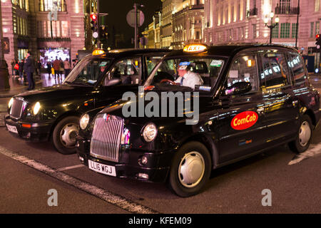 Black London taxicabs waiting for the lights to change on Piccadilly Circus, London, UK - Stock Photo