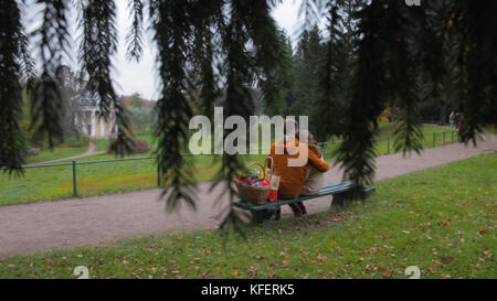 love couple on bench. Couple sitting in the park view from the branches of a tree. Young couple sitting on bench - Stock Photo
